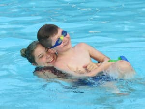 John and a counselor in the pool at Camp Royall, an autism summer camp